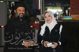 كاهن  وسيدة مسلمة يوزعان حلوى المولد النبوى ببورسعيد