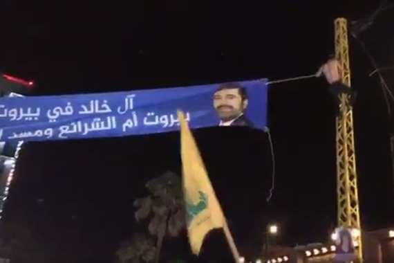 أنصار حزب الله يزيلون لافتات عليها صور رئيس الحكومة سعد الحريري